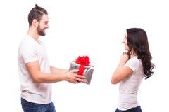 Pares jovenes felices con el presente del día de tarjeta del día de San Valentín aislado en un fondo blanco Fotografía de archivo