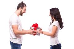 Pares jovenes felices con el presente del día de tarjeta del día de San Valentín aislado en un fondo blanco Imagen de archivo libre de regalías