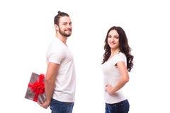 Pares jovenes felices con el presente del día de tarjeta del día de San Valentín aislado en un fondo blanco Foto de archivo libre de regalías