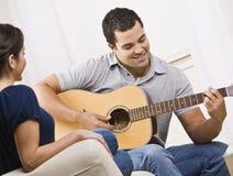 Pares jovenes felices con la guitarra Imagenes de archivo