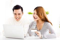 Pares jovenes felices con la tarjeta de crédito y el ordenador portátil Fotografía de archivo libre de regalías
