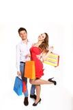 Pares jovenes felices con los bolsos de compras en el bacgkrou blanco Imágenes de archivo libres de regalías
