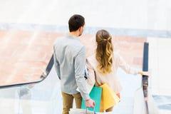 Pares jovenes felices con los panieres en alameda Fotos de archivo libres de regalías