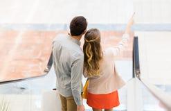 Pares jovenes felices con los panieres en alameda Imagen de archivo libre de regalías