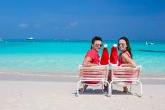Pares jovenes felices con Santa Hats roja que se sienta encendido Imágenes de archivo libres de regalías