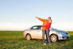 Pares jovenes felices con su nuevo coche Fotografía de archivo libre de regalías
