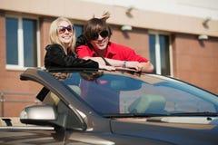Pares jovenes felices con un coche Foto de archivo libre de regalías