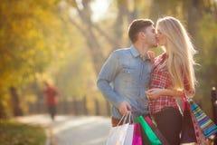 Pares jovenes felices con una bolsa de papel en el parque Imágenes de archivo libres de regalías