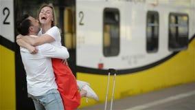 Pares jovenes felices de encontrarse otra vez en la estación de tren Funcionamientos de la muchacha para encontrar a su novio almacen de video