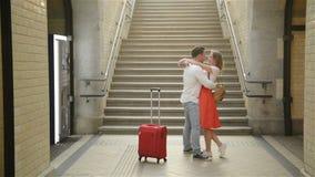 Pares jovenes felices de encontrarse otra vez en la estación de tren Funcionamientos de la muchacha para encontrar a su novio metrajes