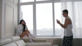 Pares jovenes felices de la familia en casa - el hasband hace la foto de su esposa en ventana con invierno de la nieve almacen de video