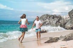 Pares jovenes felices de la luna de miel que se divierten en la playa Océano, vacaciones tropicales en la isla de Bali, Indonesia imagen de archivo
