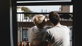 Pares jovenes felices de la visión trasera que se sientan en un pequeño balcón soleado del apartamento de Nueva York del verano,  metrajes