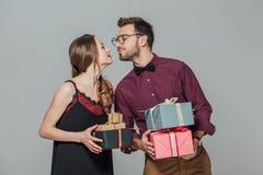 Pares jovenes felices de moda que sostienen las cajas de regalo y capaz de besarse Imagenes de archivo