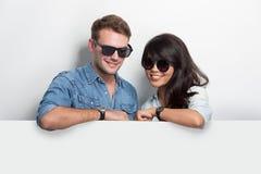Pares jovenes felices de Multiculture con la cartelera en blanco blanca Fotografía de archivo libre de regalías