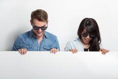 Pares jovenes felices de Multiculture con la cartelera en blanco blanca Fotos de archivo libres de regalías