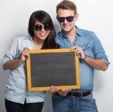 Pares jovenes felices de Multiculture que presentan con el tablero de tiza Fotografía de archivo libre de regalías