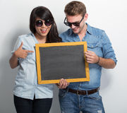 Pares jovenes felices de Multiculture que presentan con el tablero de tiza Imagen de archivo libre de regalías