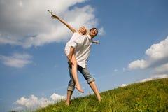 Pares jovenes felices del amor - saltando fotos de archivo