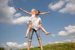 Pares jovenes felices del amor - saltando bajo el cielo imagen de archivo libre de regalías