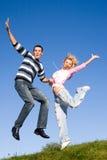 Pares jovenes felices del amor - saltando bajo el cielo azul foto de archivo libre de regalías