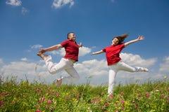 Pares jovenes felices del amor - saltando bajo el cielo azul fotografía de archivo libre de regalías