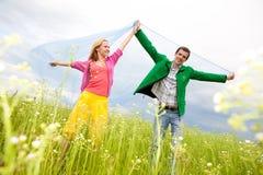 Pares jovenes felices del amor - saltando bajo el cielo azul imagen de archivo libre de regalías