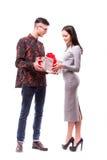 Pares jovenes felices del inconformista con el presente aislado en un fondo blanco Fotografía de archivo libre de regalías