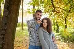 Pares jovenes felices ejoying el otoño en parque Fotos de archivo