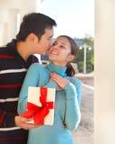 Pares jovenes felices en amor con el presente Foto de archivo