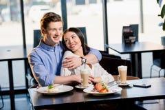 Pares jovenes felices en amor en la fecha romántica en restaurante Foto de archivo