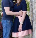 Pares jovenes felices en amor en la pared de piedra Imagen de archivo
