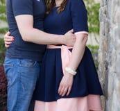 Pares jovenes felices en amor en la pared de piedra Foto de archivo