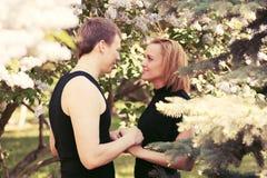 Pares jovenes felices en amor en un jardín Imagen de archivo