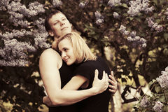Pares jovenes felices en amor en un jardín Foto de archivo
