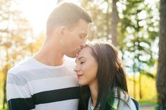 Pares jovenes felices en besarse del amor El parque al aire libre fecha Pares cariñosos foto de archivo libre de regalías