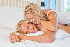 Pares jovenes felices en cama Imagen de archivo