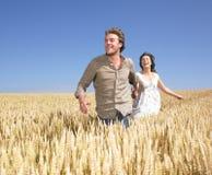 Pares jovenes felices en campo de trigo Foto de archivo libre de regalías
