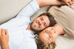 Pares jovenes felices en casa en el sofá Fotografía de archivo