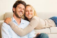 Pares jovenes felices en casa en el sofá Foto de archivo libre de regalías