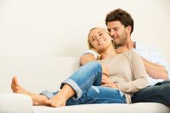 Pares jovenes felices en casa en el sofá Fotos de archivo libres de regalías