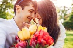 Pares jovenes felices en el amor que abraza con el ramo de la flor de la primavera al aire libre Hombre dotado su novia con los t imágenes de archivo libres de regalías