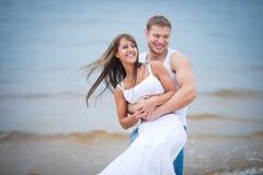 Pares jovenes felices en el amor que camina en la playa Imagen de archivo libre de regalías