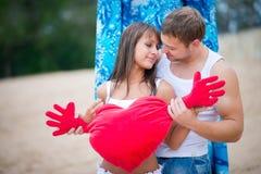 Pares jovenes felices en el amor que camina en la playa Imagen de archivo