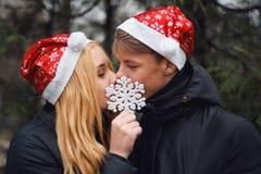 Pares jovenes felices en el amor que lleva los sombreros de Papá Noel Fotos de archivo libres de regalías