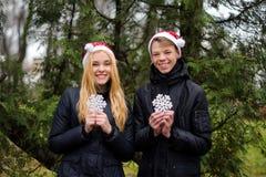 Pares jovenes felices en el amor que lleva los sombreros de Papá Noel y Imágenes de archivo libres de regalías