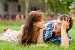 Pares jovenes felices en el amor que miente en hierba verde Fotografía de archivo libre de regalías