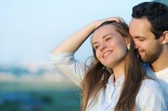 Pares jovenes felices en el amor que presenta en puesta del sol del verano Fotografía de archivo