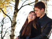 Pares jovenes felices en el amor que tiene parque del otoño de la diversión Imagen de archivo libre de regalías
