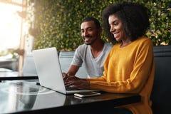 Pares jovenes felices en el café que mira el ordenador portátil fotos de archivo libres de regalías